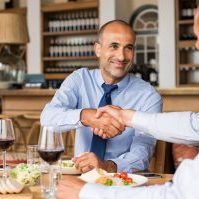 "Business people shaking hands during lunch. Happy mature businessman shaking hands with employee. Handshake confirmation done by partners for signing deal while having lunch.""r"